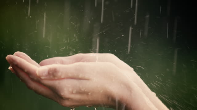 Woman enjoys and holds her hands in summer rain video