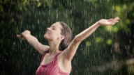 Woman enjoys and stretches her arms in summer rain video