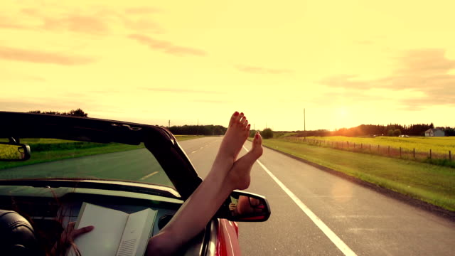 Woman enjoys freedom on the highway in car video