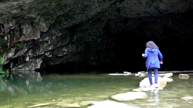 Woman entering cave video
