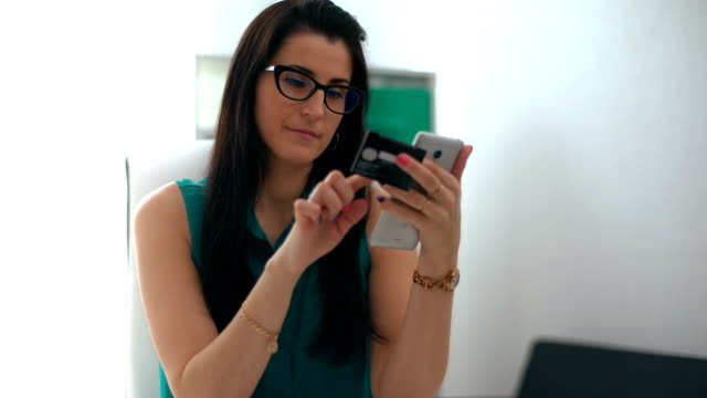 Woman entering data using smartphone while holding a credit card in the other hand video
