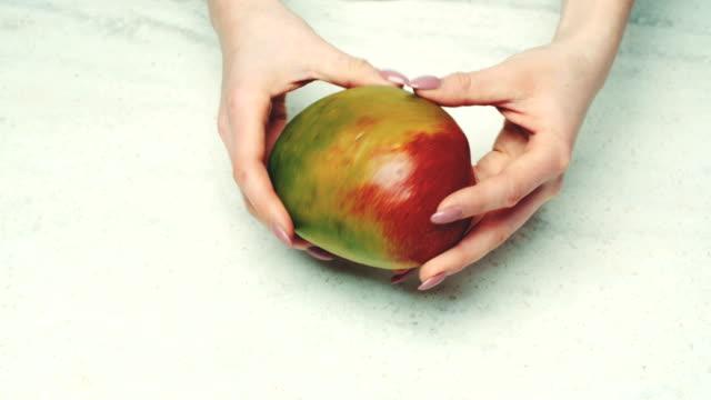 Woman Examining Fresh Mango At Counter video