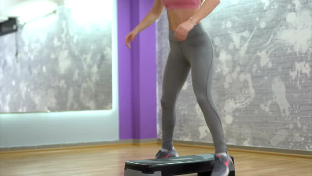 Woman exercises on aerobic stepper video
