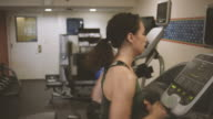 Woman exercising in fitness room on bike video
