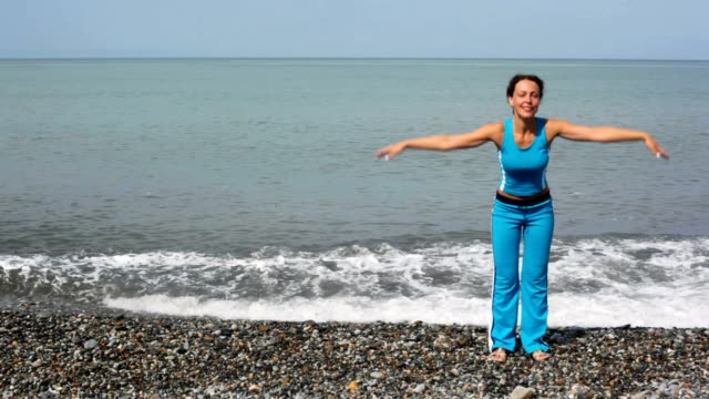 Woman exercising on beach, sea in background video