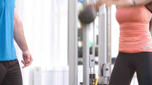 Woman exercising with a kettlebell in a gym with a trainer video