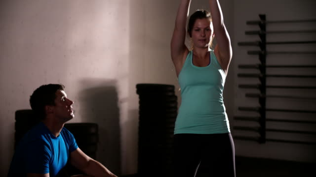 Woman exercising with personal trainer using kettlebells video