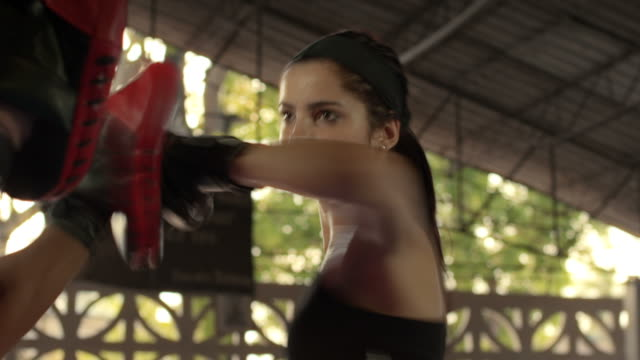 Woman exercising with trainer at boxing and self-defense lesson video