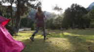 Woman exit tent, outstretches arms at sunrise video