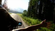Woman extends arm out of car window in mountain meadow video