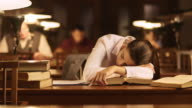 DS Woman falling asleep over books in the library video