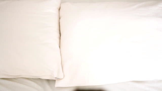Woman falling backward onto bed, slow motion video
