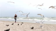 Woman feeding birds at the beach on a cloudy day, slow motion, wide shot video