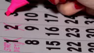 Woman fingers with pink marker crossing days on calendar. Start of diet concept video