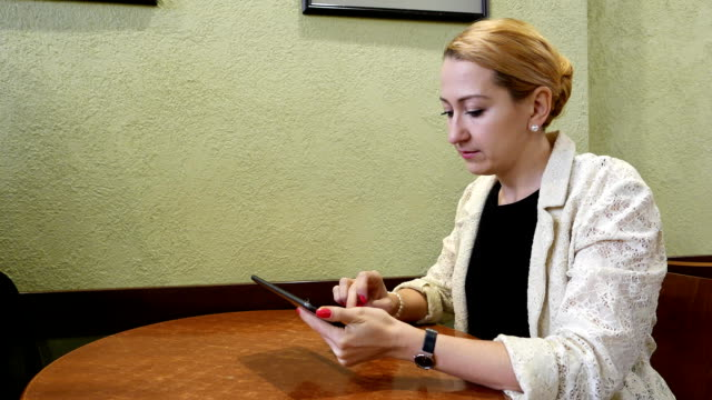 Woman finish using tablet and put it down, look to distance video