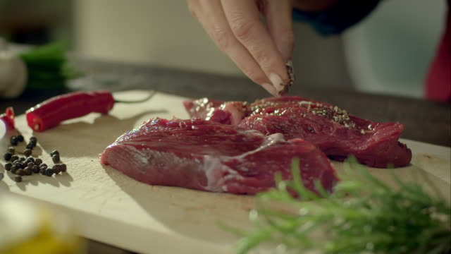 Woman flavouring a piece of meat video