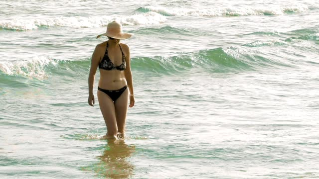 A woman flawlessly walks towards the shore video