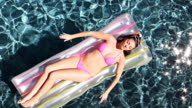 Woman Floating In Swimming Pool video