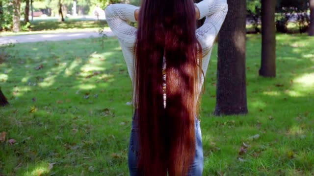 Woman flutter her luxury long hair then turn aroung and smile into camera video