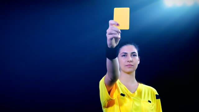 Woman football soccer referee showing penalty yellow than red card and sending player off on black background, 4k video