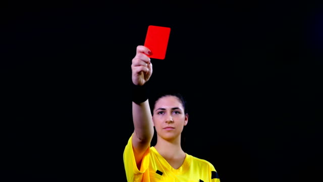 Woman football soccer referee shows penalty red card on black background, 4k video