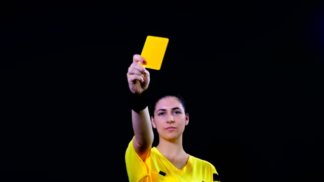 Woman football soccer referee shows penalty yellow card on black background, 4k video