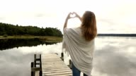 Woman frames mountain lake landscape into heart shape video