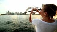 Woman framing Sydney skyline into heart shape finger frame video