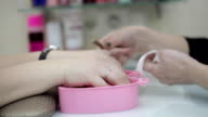 Woman gets her nails cleaned prior to getting her nails painted for her manicure video