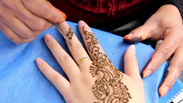 Woman Getting A Henna Tattoo On Her Fingers video