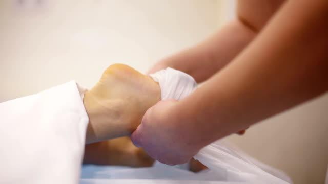 Woman getting hot stone foot massage in spa salon video