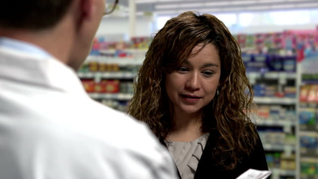 Woman getting prescription drugs from pharmacist video