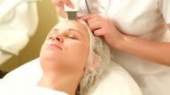 Woman getting ultrasonic face cleaning at beauty spa video