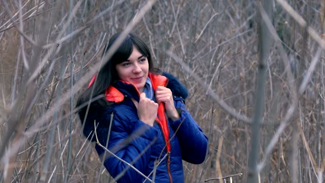 woman girl in jacket and a scarf standing in the dry branches of video