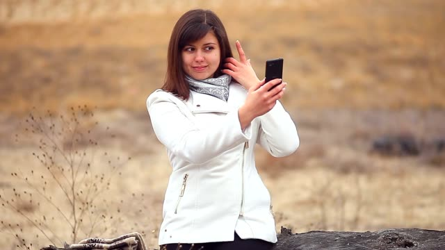 woman girl smartphone makes self phone sitting on a dry tree autumn nature video