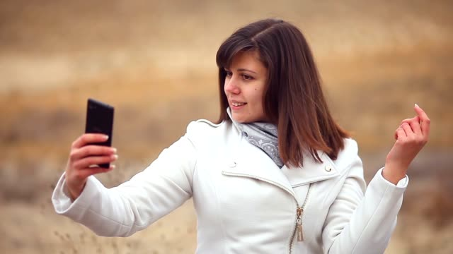 woman girl smartphone makes self phone sitting on dry tree nature autumn video