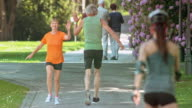 SLO MO Woman giving high five to husband running by video