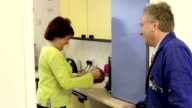 Woman Giving Plumber A Cup Of Tea In A Community Centre video