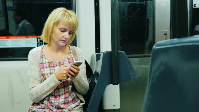 A woman goes to the metro, the smartphone uses. Past her people go video