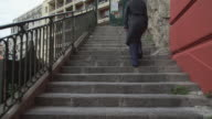 Woman going up stairs wearing coat in the city rear back view video