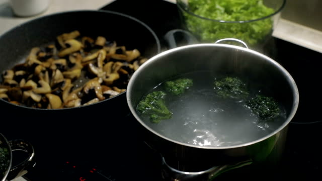 Woman hand drop colorful broccoli to the pot full of boiling water. Slow motion. Vegetarian food video