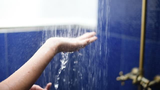 Woman hand in falling shower water. video