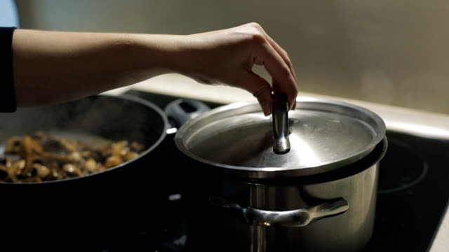 Woman hand opening the cover of pot in the kitchen. The pair is rises. Close up of a pan with colorful broccoli, pea, cauliflower in boiling water. Slow motion. Vegetarian food video