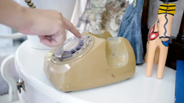 woman hand pick up old rotary style telephone on the table with vintage decorate style and dialing phone number. warm tone , retro style video