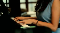 Woman hand playing piano and looking tablet video