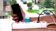 woman hand plug charger cable in extension socket and hold charging phone video