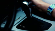 Woman hand switching gear stick in car. Driver. Transport video