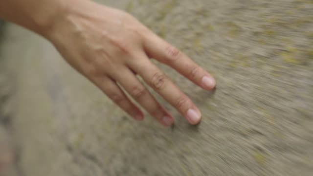 woman hand touching a sandstone wall while walking video