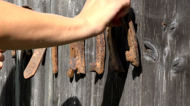 woman hand unhang rusty horse shoes from wooden retro house wall. Closeup. video