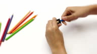 Woman hand using sharpener with color pencil on white desk video